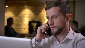 Closeup av den unga koncentrerade caucasian affärsmannen som har en diskussion på telefonen som framme sitter av bärbara datorn stock video