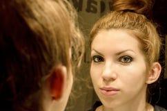 Ung kvinna i avspegla Arkivbild