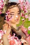 Closeup av den unga kvinnan i persikaträdgård Arkivfoto