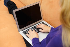 Closeup av den unga kvinnan som använder bärbara datorn på soffan Arkivfoto