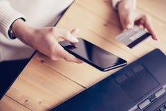 Closeup av den unga kvinnan som gör online-shopping vid bärbara datorn och smartphonen på arbetsplatsen Flicka som hem på trycker Fotografering för Bildbyråer