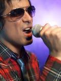 Closeup av den unga mannen som sjunger in i mikrofonen Royaltyfri Fotografi