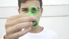 Closeup av den unga pojken som spelar med rastlös människaspinnaren som snärtar och rymmer snurrapparaten i hand - lager videofilmer