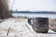 Closeup av den unika handgjorda koppen med det folk tecknet med den suddiga sjön på bakgrund arkivbild