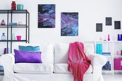 Closeup av den vita bekväma soffan med rosa färgfilten och purpurfärgade och blåa kuddar i den moderna vardagsruminre, verkligt f royaltyfria foton