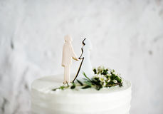 Closeup av den vita bröllopstårtan med bruden och brudgummen Figure Toppe Arkivfoto