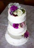 Closeup av den vita bröllopstårtan med det bruna bandet och blommor överst Royaltyfria Foton
