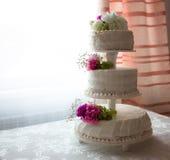 Closeup av den vita bröllopstårtan med det bruna bandet och blommor överst Arkivfoto