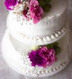 Closeup av den vita bröllopstårtan med det bruna bandet och blommor överst Arkivbild
