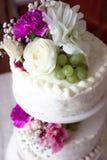 Closeup av den vita bröllopstårtan med det bruna bandet och blommor överst Royaltyfri Bild