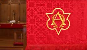 Closeup av det röda kyrkliga banret med det oskarpa altaret in bakom fotografering för bildbyråer