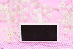 Closeup av det tomma svart tavlatecknet med vita blommor, på rosa bakgrund Royaltyfria Foton