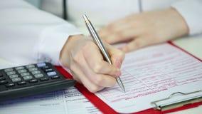 Closeup av doktors händer som fyller i sjukförsäkringreklamationsform som kontrollerar kostnader arkivfilmer