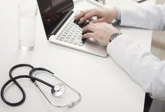 Closeup av doktorshänder på bärbar datortangentbordet arkivfoton