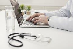 Closeup av doktorshänder på bärbar datortangentbordet royaltyfria foton