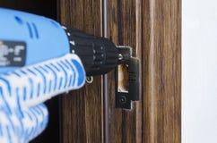 Closeup av elektrisk skrewdriver, manlig hand i handskar genom att använda den för att reparera en del av dörrhandtaget, lås arkivbilder