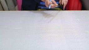 Closeup av en äldre kvinna i en möblemangfabrik som är mäta och markera ett grått material för soffan med en kil arkivfilmer