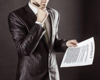Closeup av en affärsman som rymmer en penna och ett dokument med uttrycken av avtalet Arkivbild