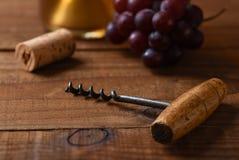 Closeup av en antik korkskruv med ut ur fokuskork, druvor och en flaska av vitt vin i bakgrunden royaltyfria foton