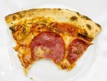 Closeup av en biten del av pizza på en vit platta arkivbilder