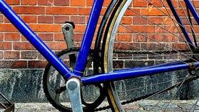 Closeup av en blå cykel på en bakgrund för vägg för röda tegelstenar - cykelkedjedetalj arkivfoto