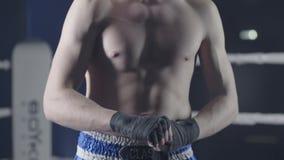 Closeup av en blandad kampsportkämpe som slår in hans händer för en kamp Boxaren slår in hans hand som ett rött förbinder för stock video
