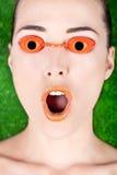 Closeup av en förvånad härlig kvinna som bär garva sängexponeringsglas Arkivbilder