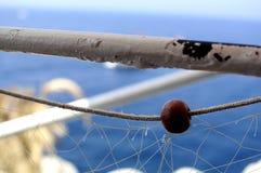 Closeup av en fisknäthängning på en vit pol på ett skepp på sjösidan med en blå bakgrund royaltyfri foto