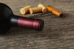 Closeup av en flaska av Cabernet - sauvignon vin med korkskruvet och korkar på en lantlig trätabell royaltyfria foton