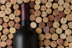 Closeup av en flaska av Cabernet - sauvignon vin som omges av använda korkar royaltyfria foton