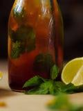 Closeup av en fuktig flaska av kallt te med sidor av mintkaramellen och halvor av limefrukt En glasflaska med en förnyelse coolt arkivfoto