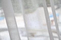 Closeup av en gardin på en stång på stranden Arkivfoton