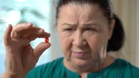 Closeup av en hög kvinna med den röda preventivpilleren stock video