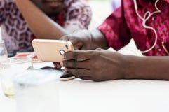 Closeup av en hand som rymmer en mobiltelefon med en person i lodisarna royaltyfri bild