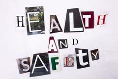 Closeup av en hand som skriver ett meddelandeord som skriver HÄLSA och säkerhet som göras av olika bokstäver för tidskrifttidning royaltyfri fotografi