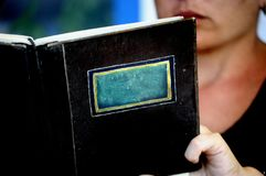 Closeup av en isolerad bok eller manu med ingen titel med en person som läser bakom på bakgrunden - utrymme för att skriva royaltyfria bilder