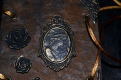 Closeup av en kamé och rosor på enseende handgjord anteckningsbok arkivfoton