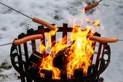 Closeup av en lägereld med varmkorvmat över öppen brand Utomhus- plats för vintersnö royaltyfri fotografi