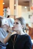 Closeup av en makeupkonstnär som applicerar makeup Arkivfoton