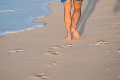 Closeup av en mans kala fot som går på en strand på solnedgången, med en våg royaltyfri fotografi