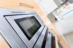 Closeup av en modern ugn i ett lyxigt kök som fixas till det trä arkivbild