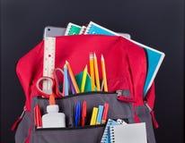 Closeup av en ryggsäck med skolatillförsel royaltyfri bild