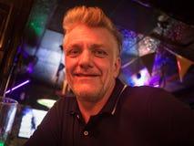 Closeup av en stilig caucasian man som sitter i en bar fotografering för bildbyråer
