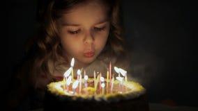 Closeup av en ung flicka som ut blåser födelsedagstearinljus arkivfilmer