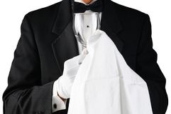 Closeup av en uppassare i smokingen som polerar ett vinexponeringsglas royaltyfri foto