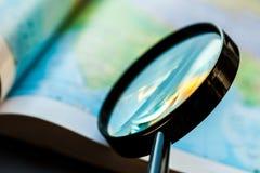 Closeup av ett förstoringsglas på en kartbok fotografering för bildbyråer