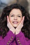 Closeup av ett flickainnehav som hon vänder mot och att le Royaltyfri Foto