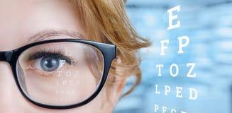 Closeup av ett kvinnligt öga med exponeringsglas och en siktprovtabell royaltyfria foton