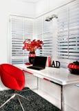 Closeup av ett modernt arbetsrum med en röd stol en vit tabell inc royaltyfri bild