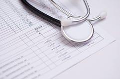 Closeup av ett svart stetoskop på medicinsk analys Royaltyfri Fotografi
